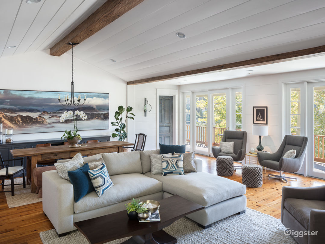 Great room with wood beams and rock fireplace. Lake views and large outdoor deck accessible.