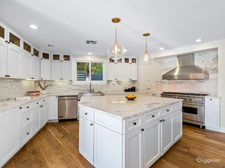 Large island in chef kitchen with marble countertops and all viking appliances.