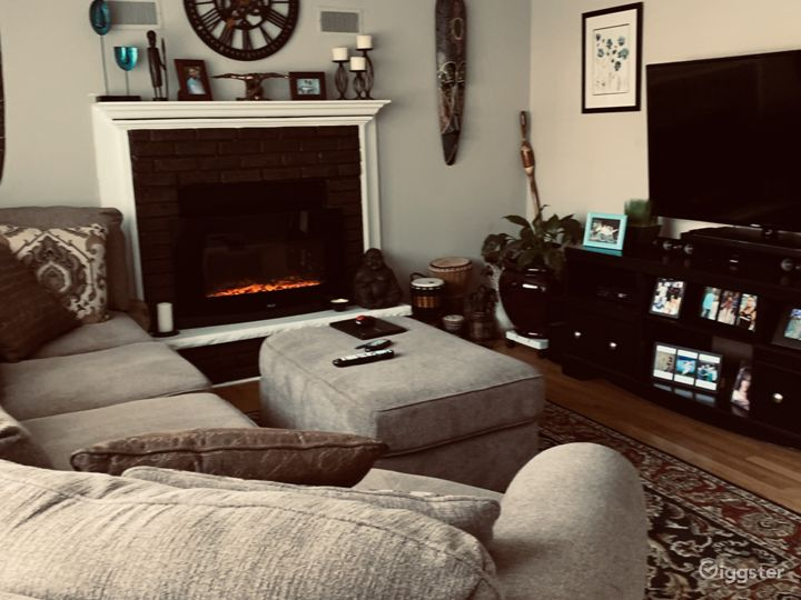 Living room with African art and mantle fireplace.