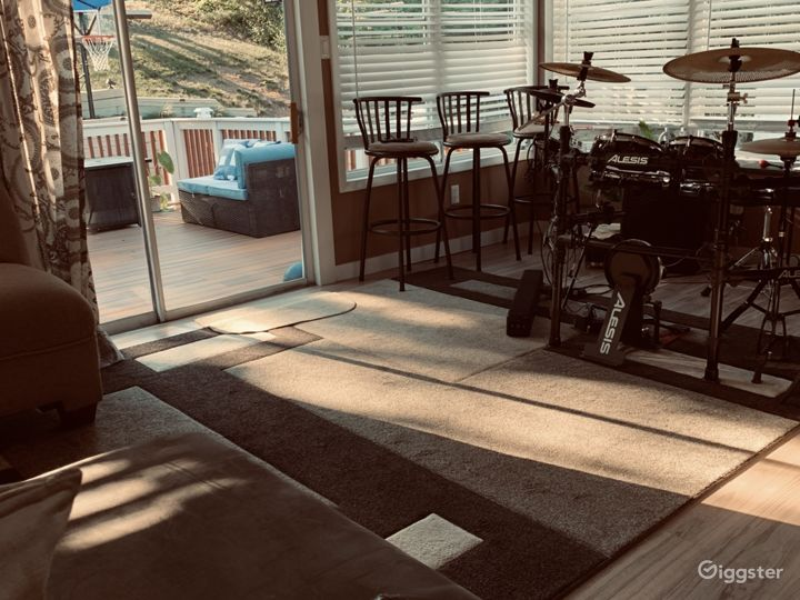 Porch with sliding door out to deck. Drums on the side.