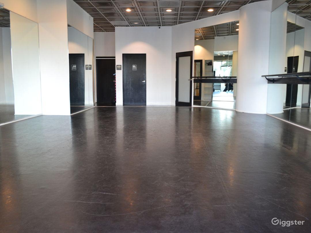 Dance studio with view of private bath door, office door, and back door.