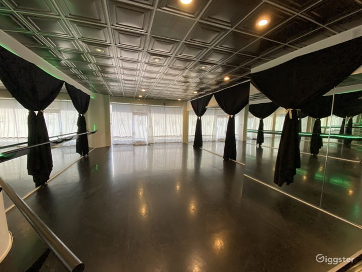 Dance studio with white curtains over front windows. When open offers beautiful view above balcony