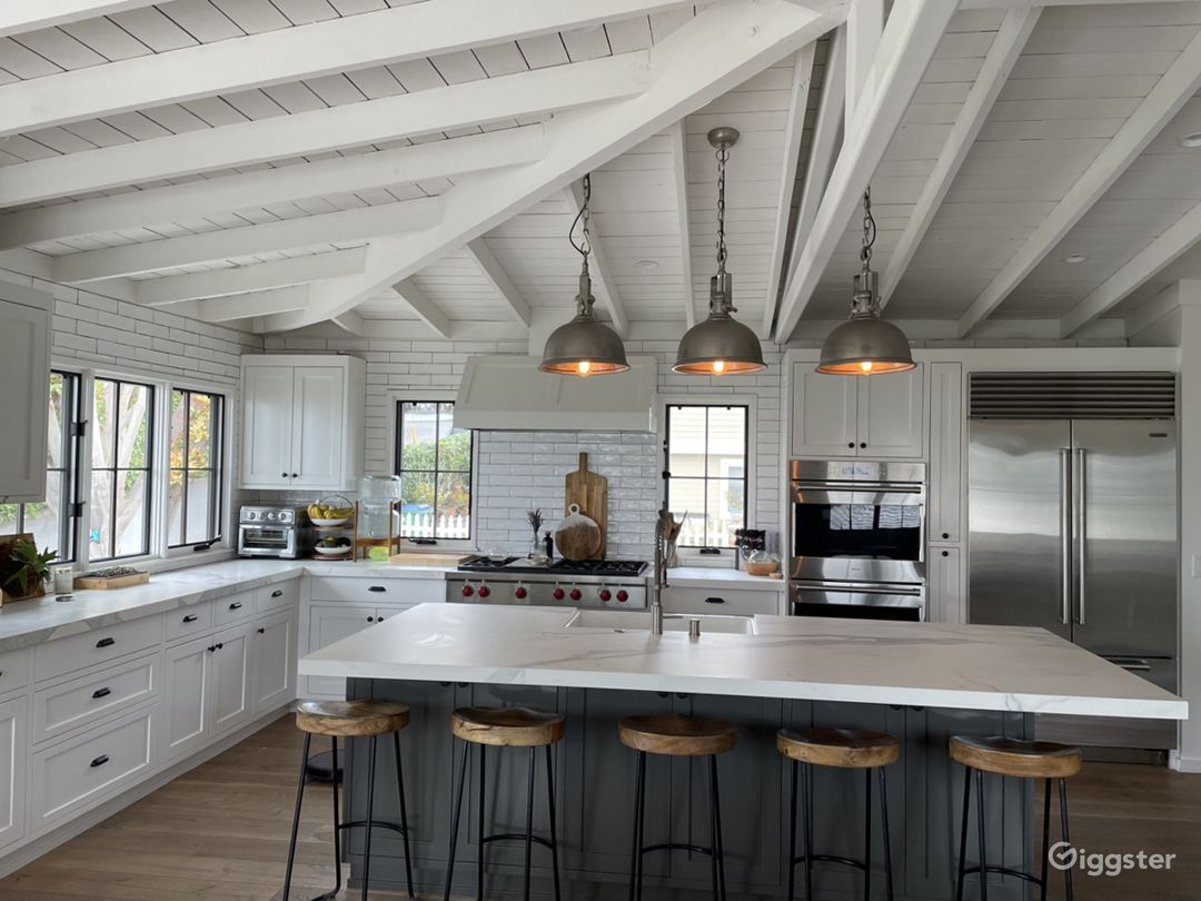 Farmhouse Kitchen Sink, huge Island, Rustic Wood flooring, Stainless steel appliances and large picture windows.