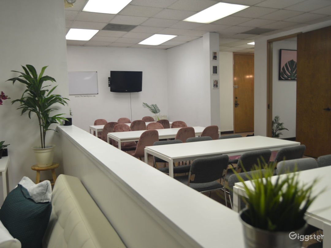 Overlooking couch & lounge area- and larger conference area with mounted TV, whiteboard, tea station, and projector.
