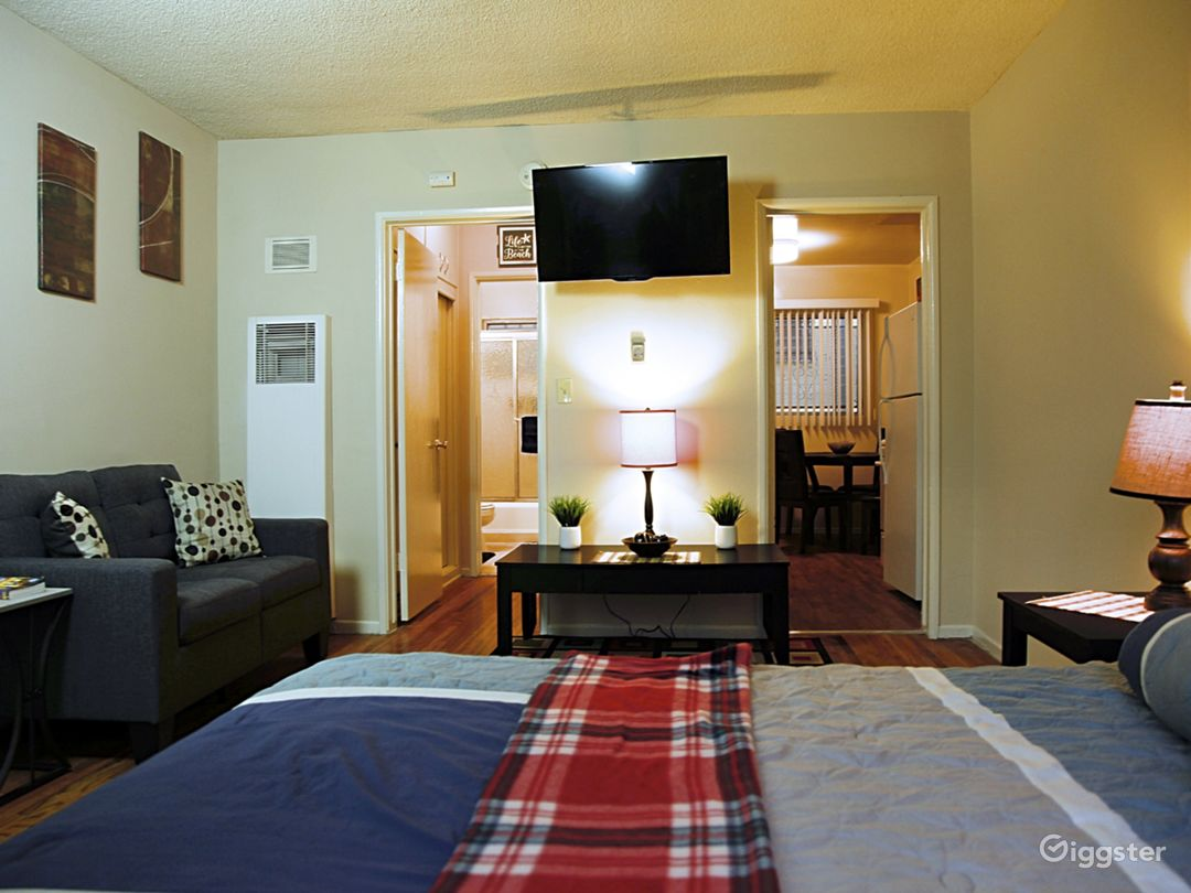 Studio Bedroom with love seat couch, small desk across from bed and 41in wall mounted TV.