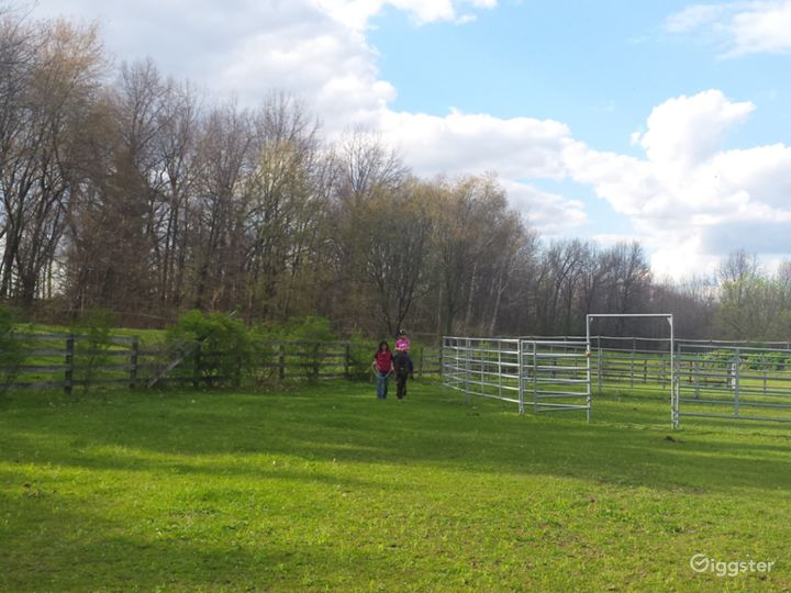 Outdoor arena 100'x200' with 50' diameter rodeo grade 6' high round pen. Grass footing, riding area/spectator seating on hilly area to left