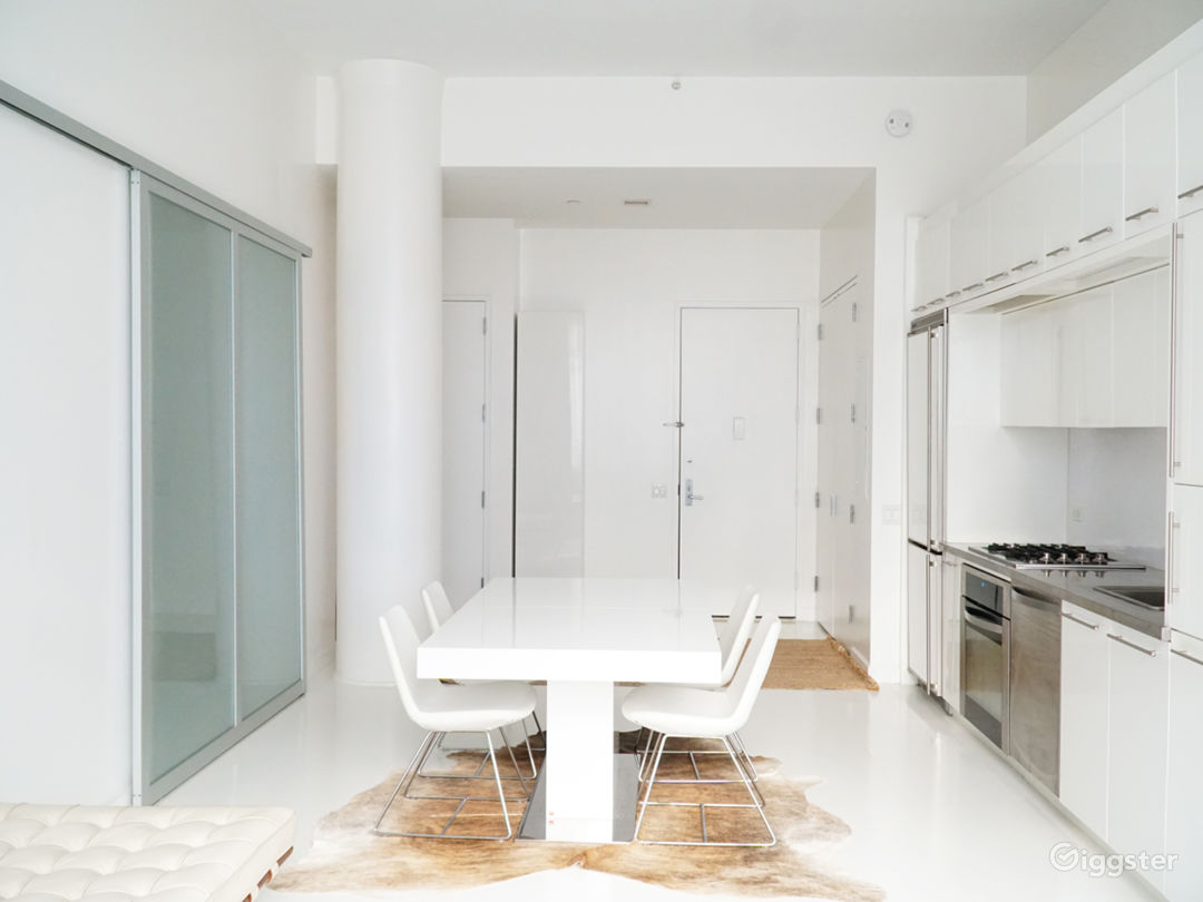 Opening Dining Room  with large column & sliding glass wall, 14ft ceilings,white floor  cowhide rug, white lacquer table