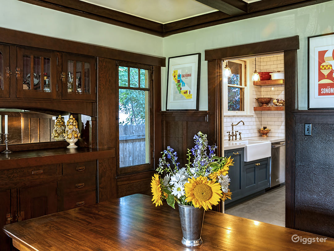 Dining room with original wood buffet, windows, embossed leatherette wainscoting between battens