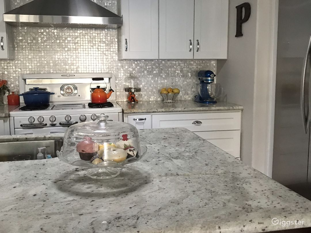 The vintage 1940s stove adds charm to the chef kitchen that features beautiful Mother of Pearl black splash, granite countertops, stainless steel appliances, and vintage 1940s o'Keefe and Merritt stove
