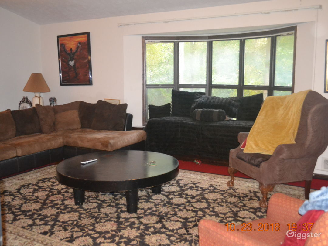 Family room with large bay window, bench, storage spot.