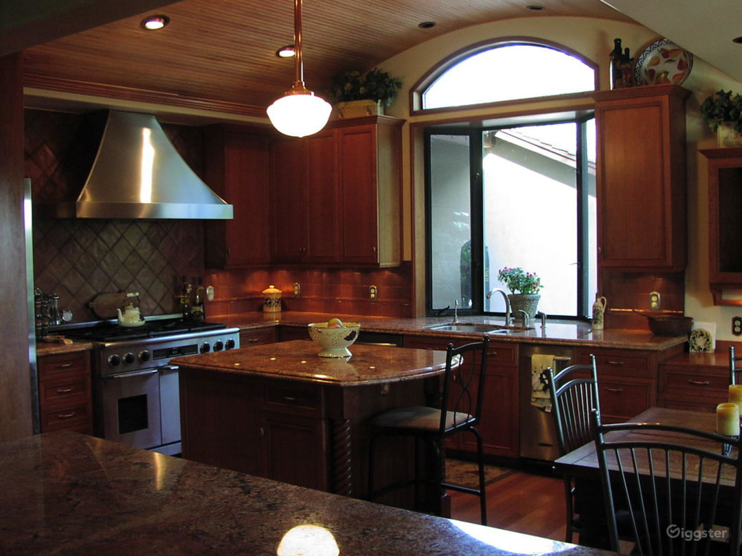 Kitchen with arched wood ceiling, stainless appliances, cherry cabinets, copper tile and granite counters
