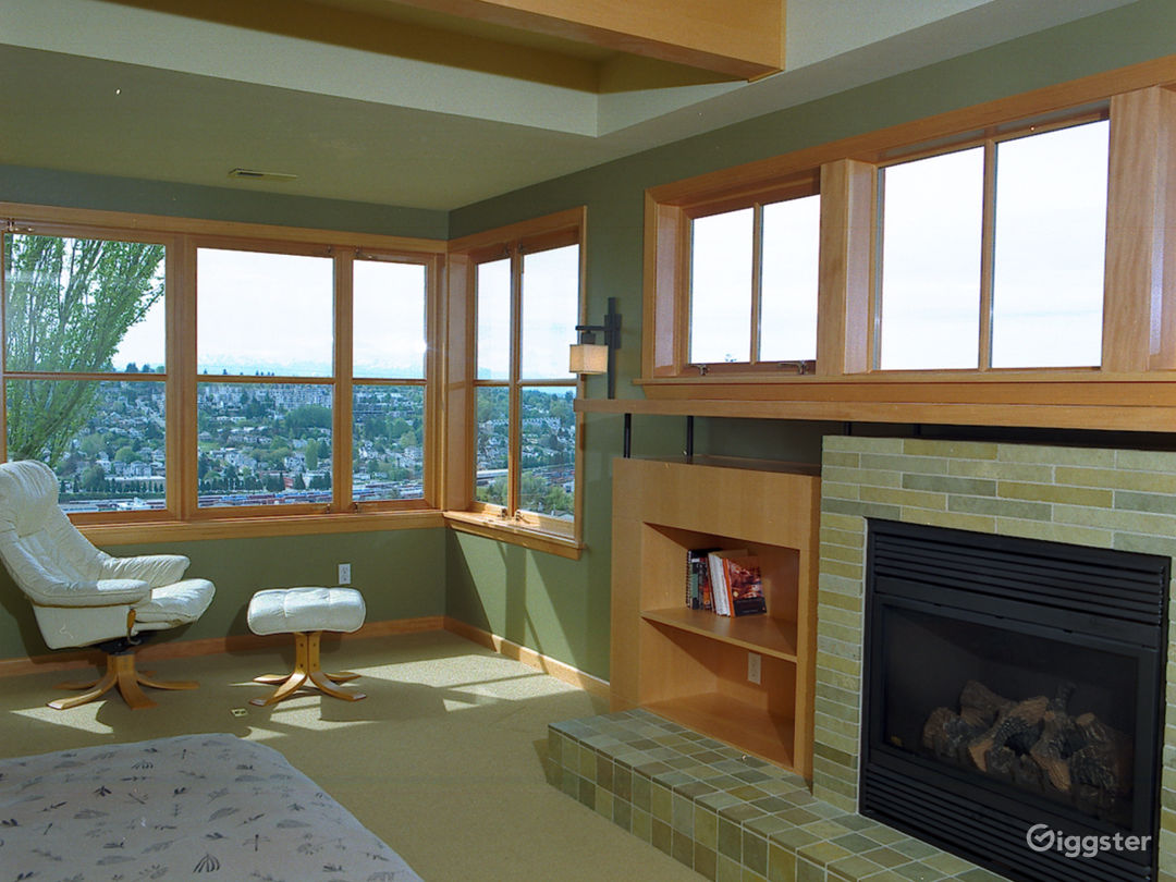 Master bedroom with fireplace and western view of Puget Sound and Olympic Mountains