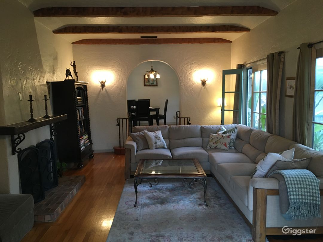 Spanish-style living room with beamed ceilings and rounded archways.