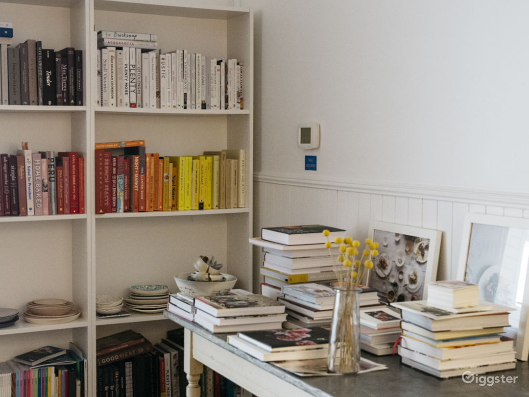 Cookbook shelves in the entry way. There is a zinc-top table to use for shoots and a wood table that is 8 feet long.