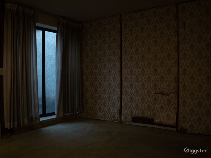Empty Bedroom with vintage wallpaper and ugly wood paneling underneath.