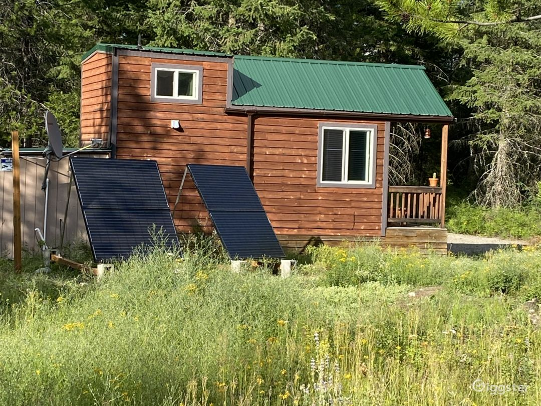 South side showing the porch, loft, solar panels, utilities shed and satellite dish.