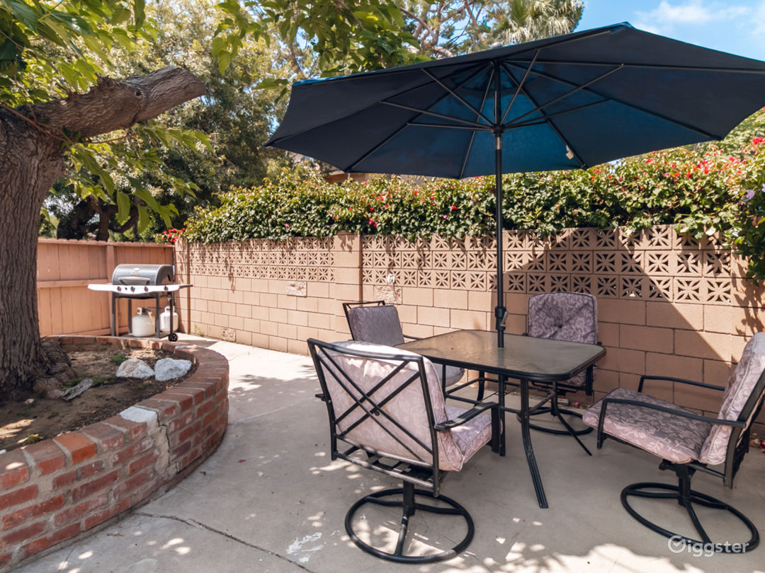 Includes table with shade umbrella, mature shade tree, barbeque