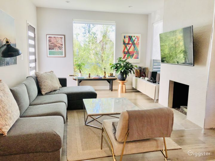 Bright living room featuring giant window overlooking front lawn, L-couch, marble coffee table, record player/records, 55-inch flat screen and ethanol fireplace.