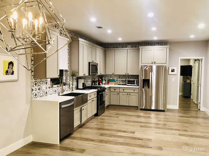 Giant, gleaming kitchen with brand new appliances and custom fleur-de-lis tiles.