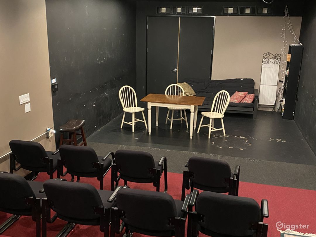 View of the stage with table and chairs, couch and a prop shelf.