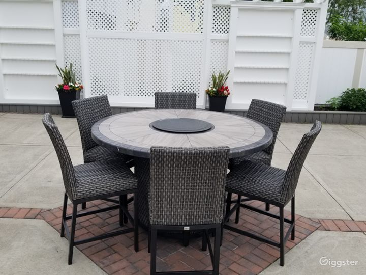 Eating area in backyard with 2 champagn walls and decorative wall in middle.