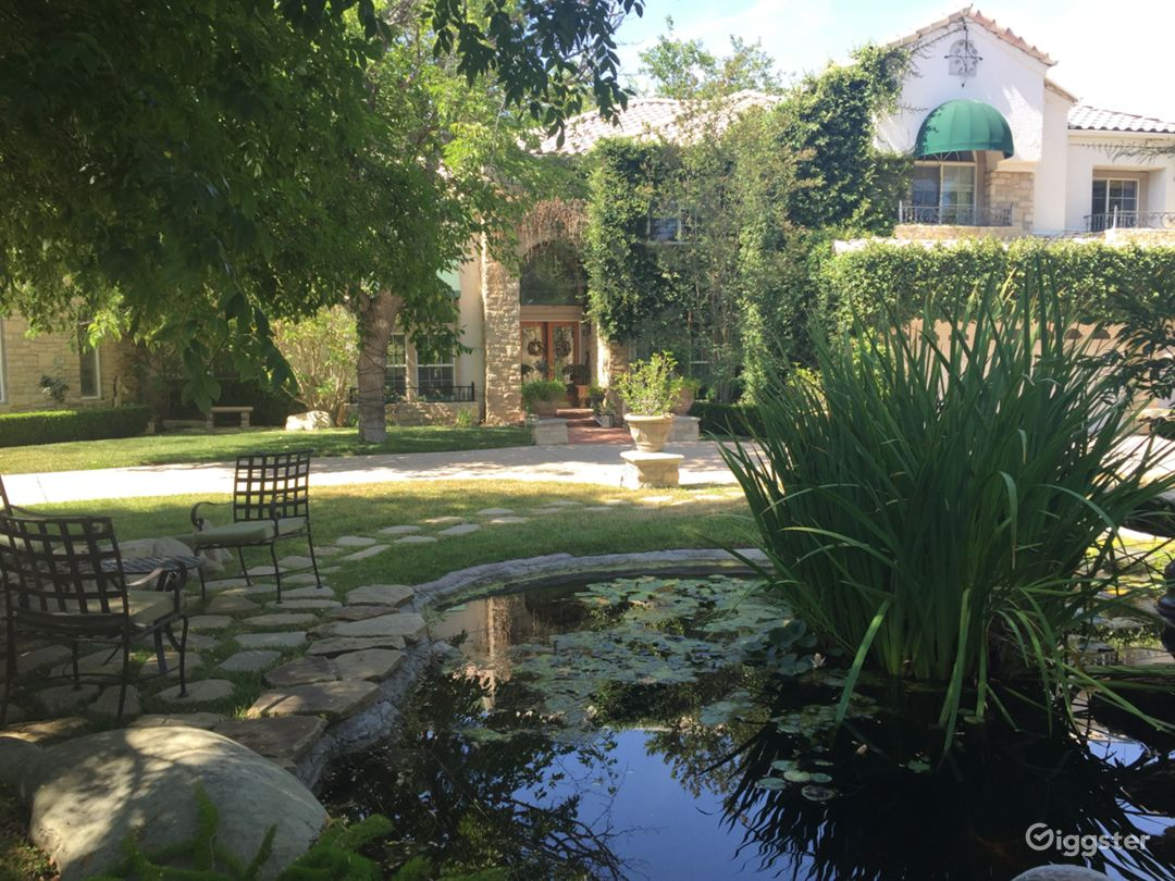 Front view. A circular driveway with wrought iron gates at both sides. Koi pond with fountain in front yard