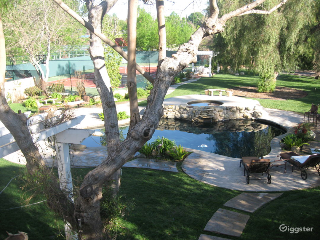 Backyard pool view, with tennis court in the background