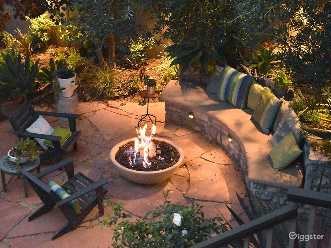 The property features an award winning garden with a   gorgeous stone bench and fire pit. Sip drinks by the pool or sit by the glow of a warm fire at night. The two-story rear studio and staircase also offer spectacular camera angles for the perfect shot.