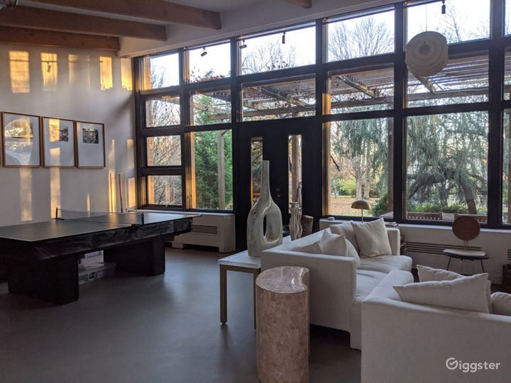 Sun filled living room with vaulted ceiling, exposed beams, picture windows, wood burning fireplace with original marble surround and polished concrete floors.