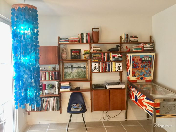 Downstairs -- vintage pinball, Cato wall unit, Eames chair, Panton shell lamp