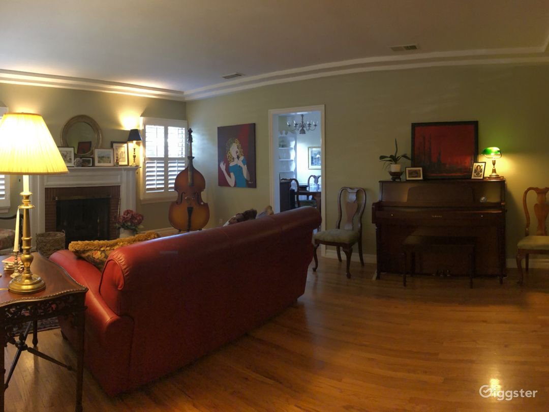 Living room with piano, bookshelves, gas fireplace