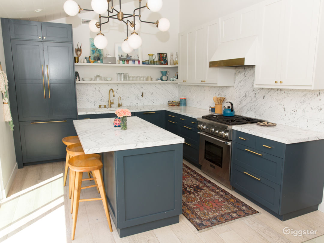Modern kitchen with marble countertops, brass handles, beautiful light fixtures and great decor.