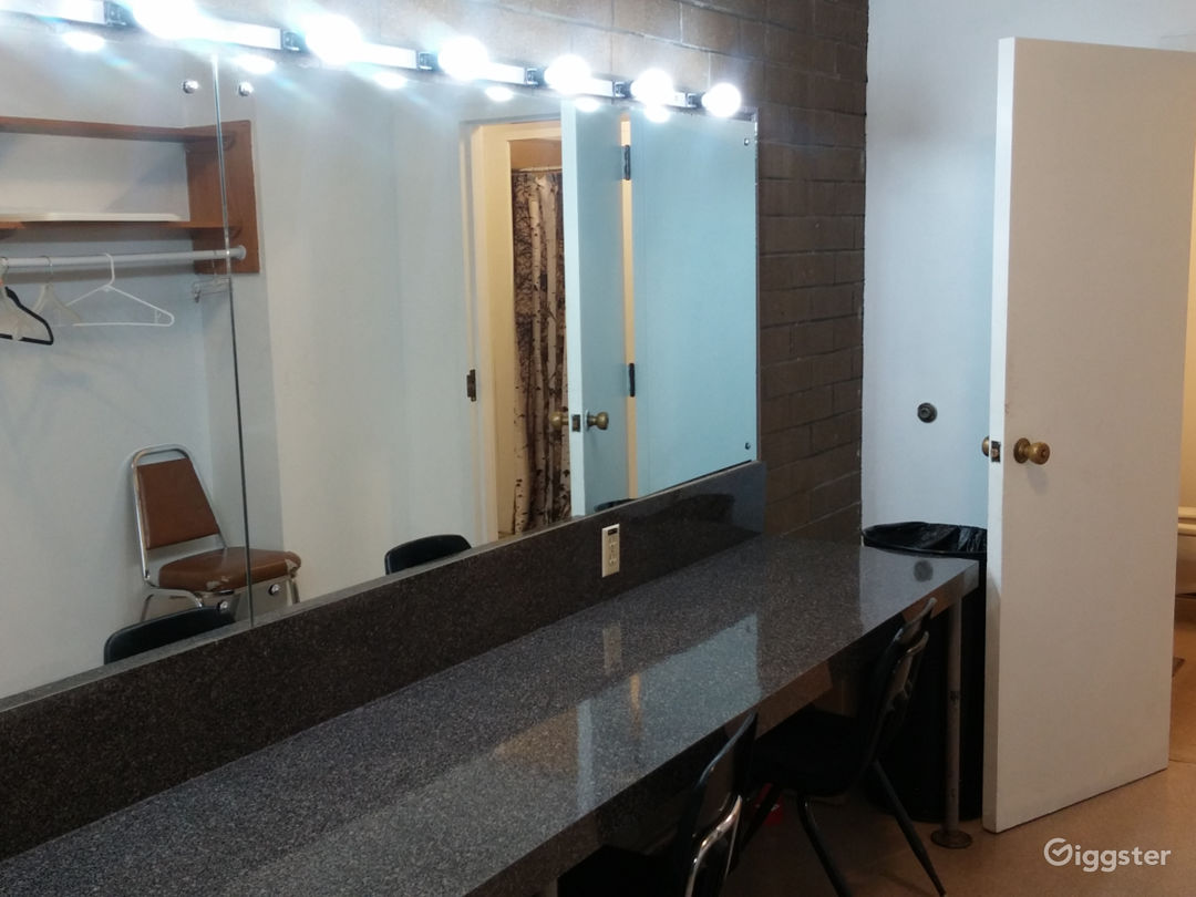 Two identical dressing rooms backstage with room for 10, shower and toilet, make-up mirror and garment rack.
