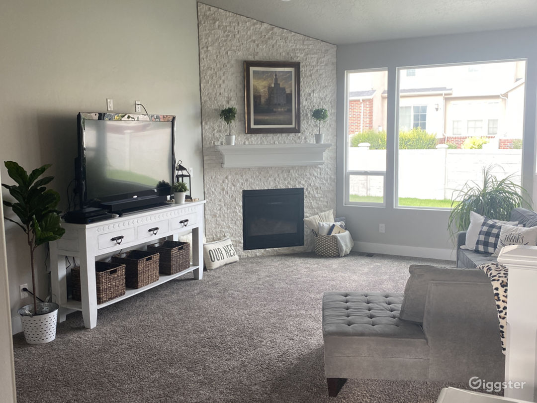 Family room with gray wrap around couch and white fireplace