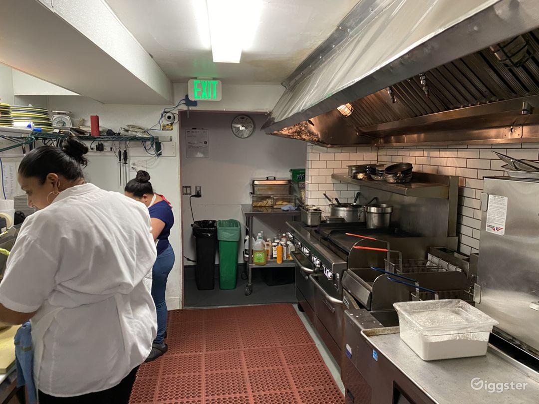 Kitchen with range, ovens, deep fryers, low boy mise-en-place.