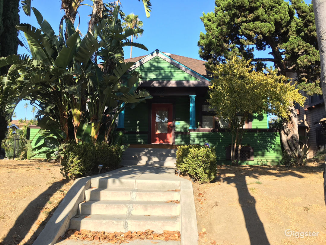 Green Craftsman style house with blue trim and orange door. Single story home.
