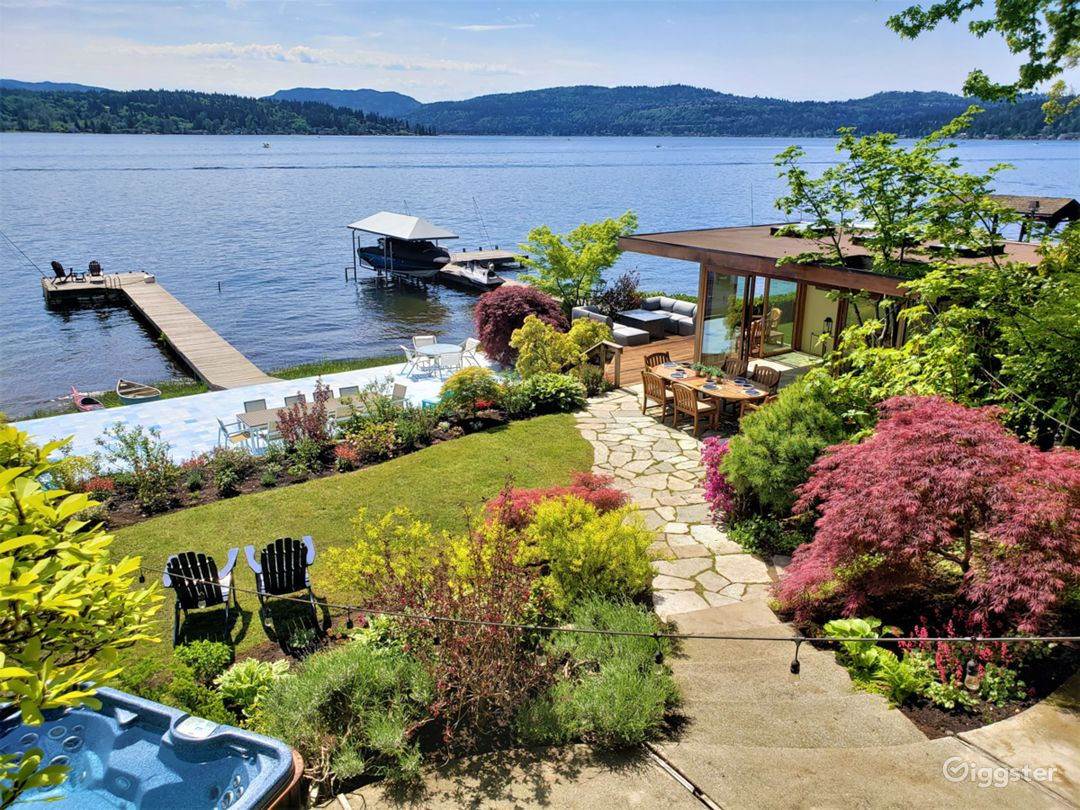 Directly on the lake with 75 feet of waterfront, the property features extensive gardens and a renovated boathouse/bar.