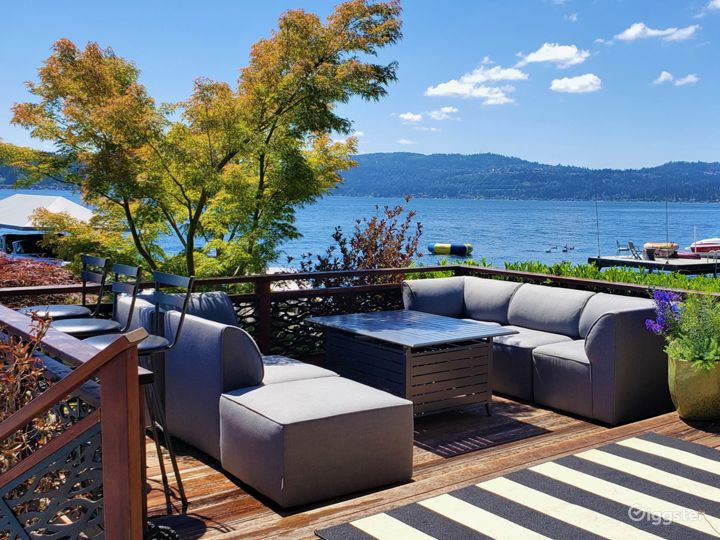 A sliding door on the east side of the boathouse opens to a deck with comfortable outdoor furniture and a fire table.