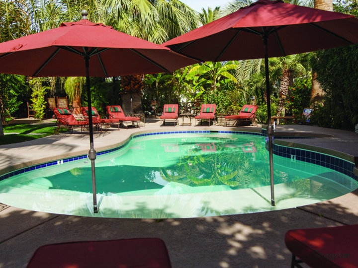 Solar powered saltwater pool and jacuzzi surrounded by tall walls, swaying palms and lush landscaping.