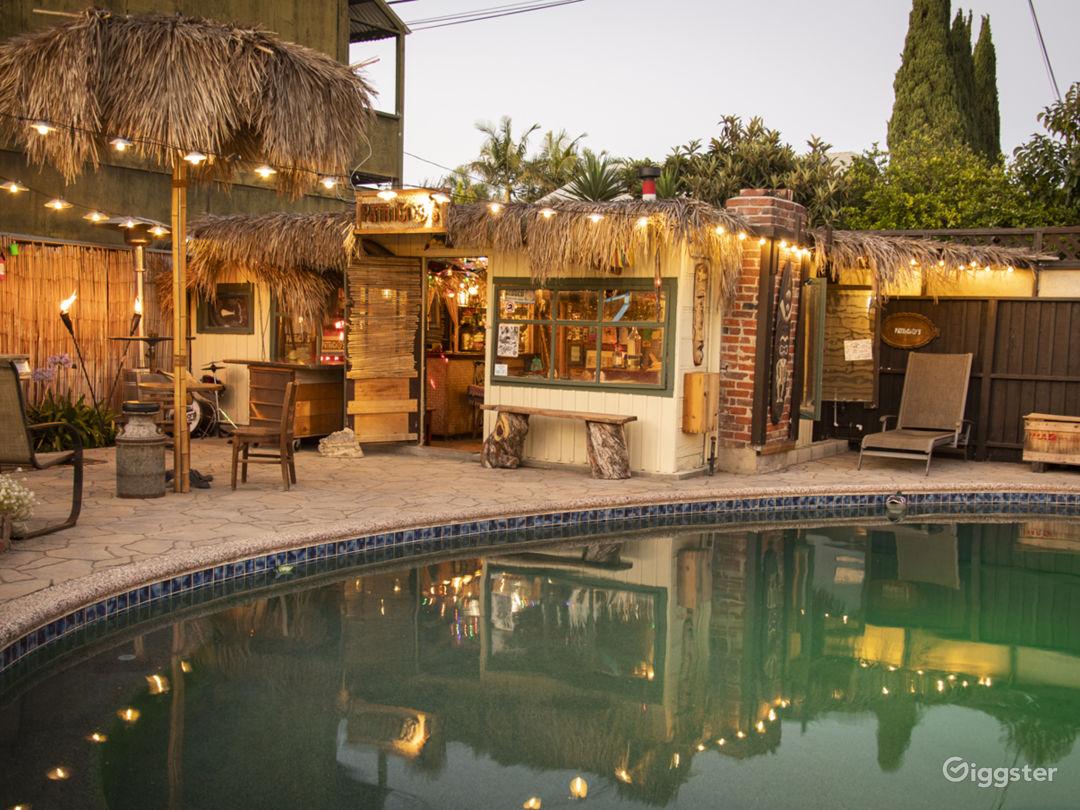 Vintage backyard with tiki bar, pool, and pond Photo 5