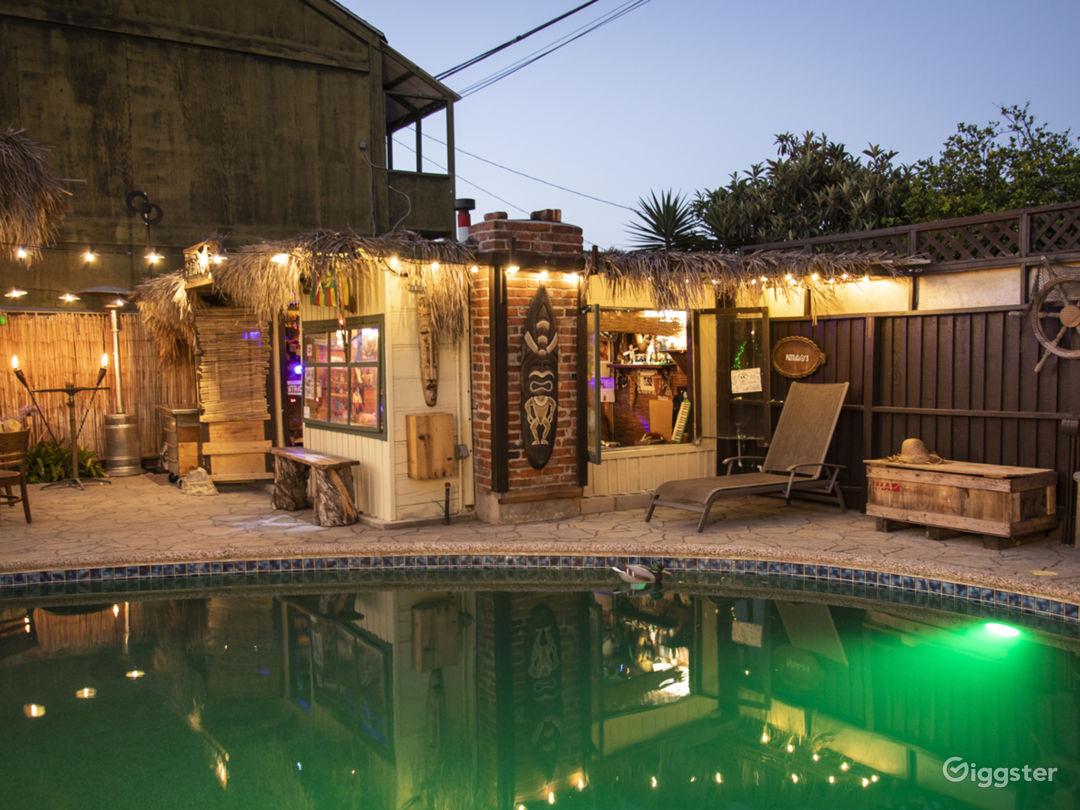 Vintage backyard with tiki bar, pool, and pond Photo 4