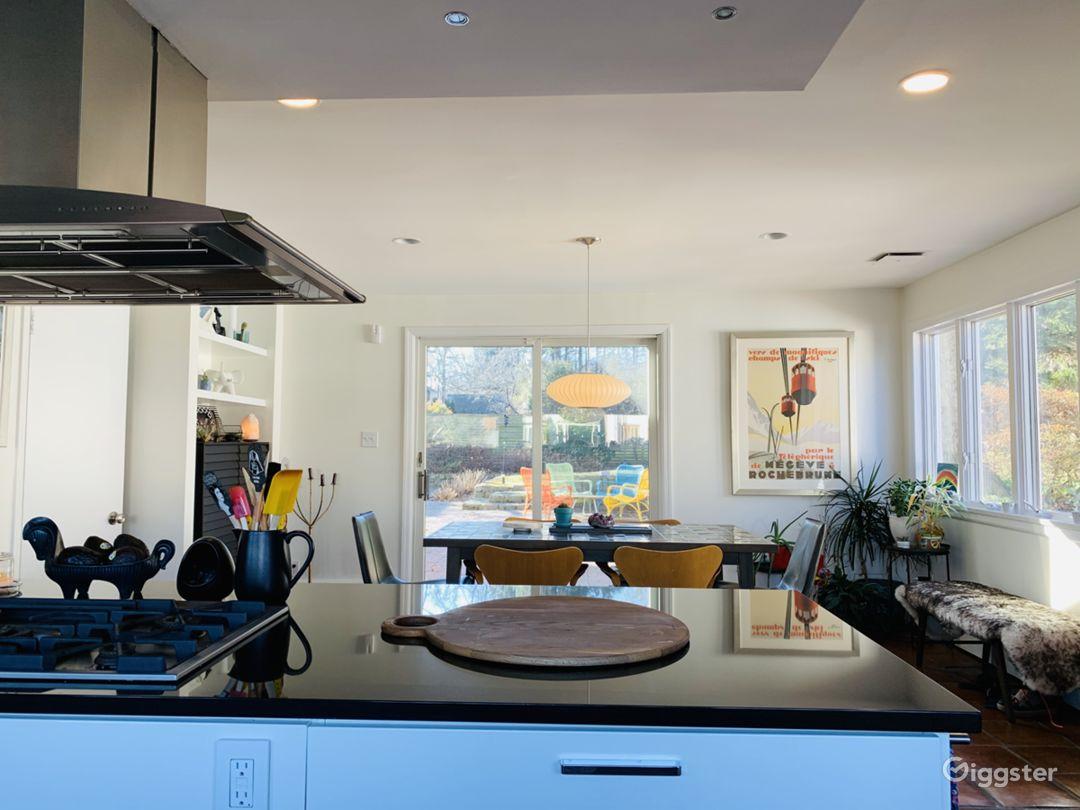Kitchen with view through glass sliding door to courtyard-garden