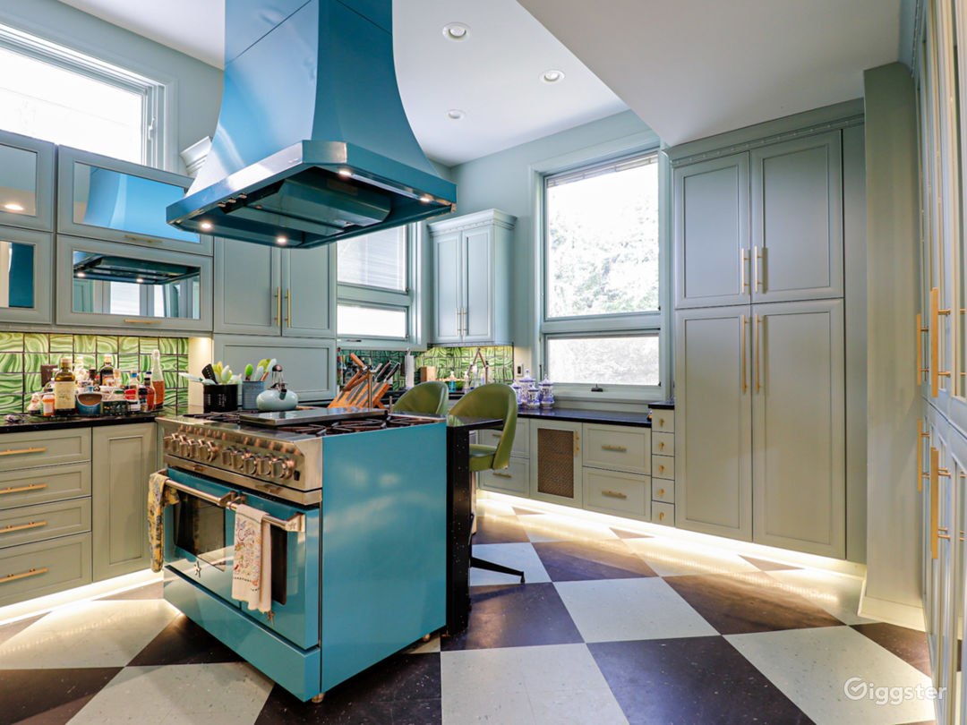 Turquoise and emerald period kitchen with harlequin floor, colored appliances, faux malachite backsplash.