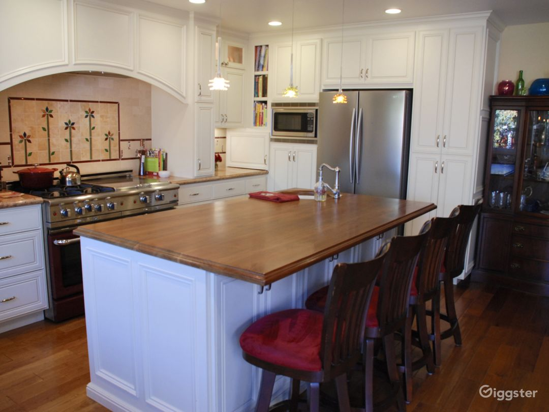 Walnut island with sink, granite on the countertops.