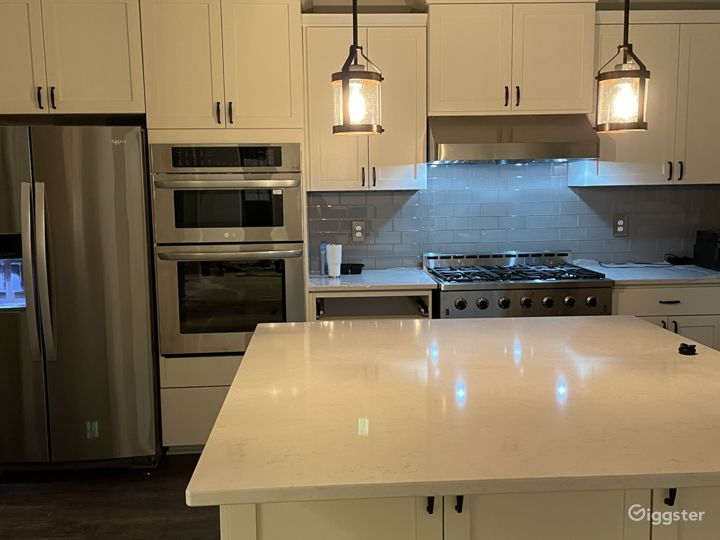 Large White quartz counter top with stainless steel appliances and gray glass tile backsplash