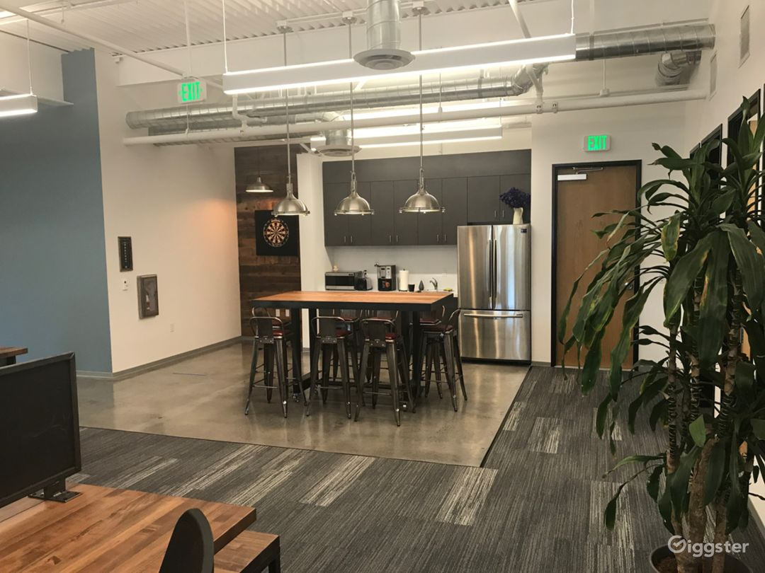 View from southwest side of office showing kitchen area and darts. Inside offices are on the right. Conference room and private offices to the left.