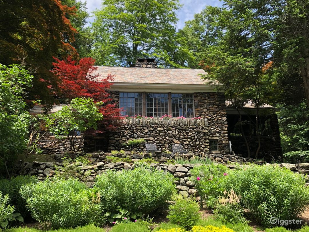 View of the back of the stone cottage. It faces the main house, and is atop a hill.