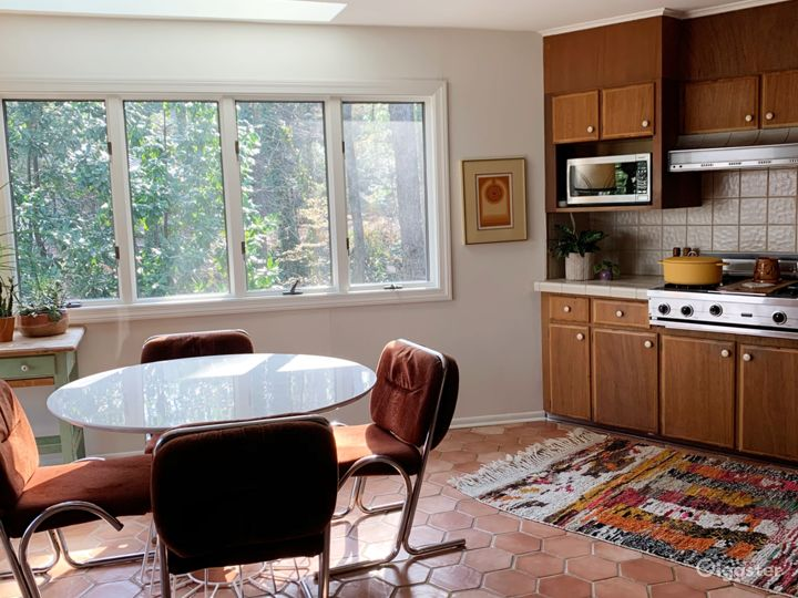 """Kitchen view of eating area and 36"""" vintage viking gas range."""