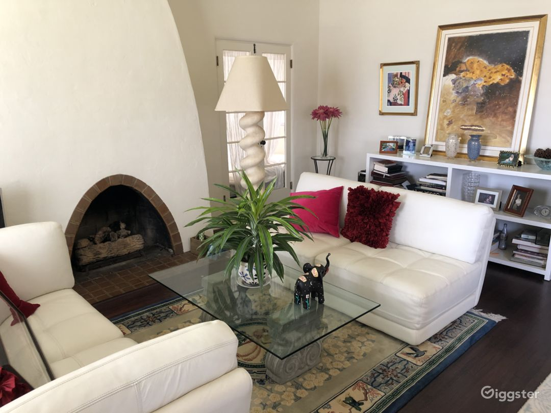 View from front door.  Back Glass door behind lamp enters office and a second back door to side patio.  Side patio is a great production set up area or staging area for talent.  Photo below.  Fireplace is gas. Arches complement home throughout.