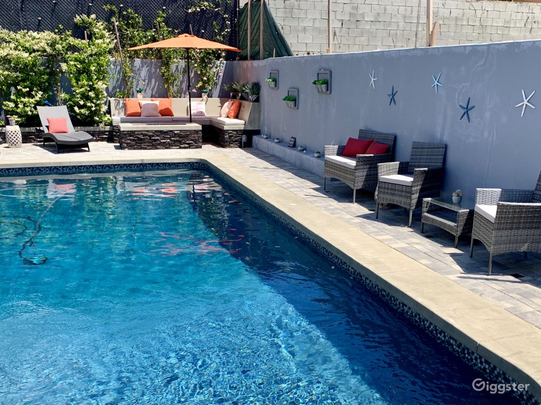 Backyard with pool, fire-pit and bench, gas bbq and sitting/dining area.